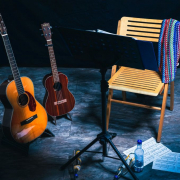 Auf einer Bühne stehen zwei Gitarren im Ständer neben einem leeren Stuhl, der hinter einem Notenständer steht.