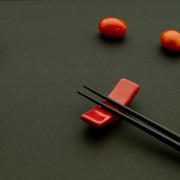 Auf dem Foto im Querformat befinden sich zwei Essstäbchen, die auf einem roten Bänckchen liegen. Eine Datteltomate ist im Visier der Stäbchen, weitere Tomaten stehen in einer Warteschlange bis sie an der Reihe sind