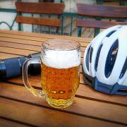 Auf einem Gartentisch steht ein voller Bierkrug eingerahmt von Fotoapparat und Fahrradhelm